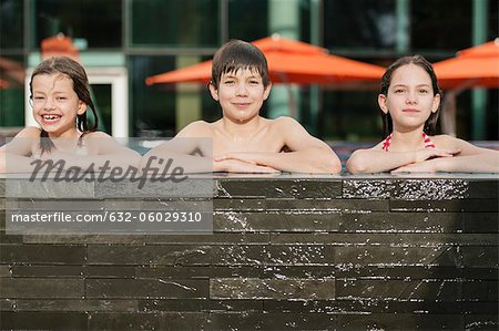 Siblings leaning on edge of swimming pool side by side, smiling, portrait Stock Photo - Premium Royalty-Free, Image code: 632-06029310