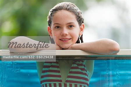 Girl in bikini leaning on edge of swimming pool, smiling, portrait Stock Photo - Premium Royalty-Free, Image code: 632-06029438