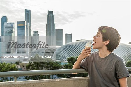 Boy eating ice cream cone, city skyline in background Stock Photo - Premium Royalty-Free, Image code: 632-06029449