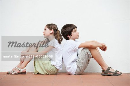 Boy and girl sitting back to back listening to music together Stock Photo - Premium Royalty-Free, Image code: 632-06029668