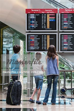 Children looking at arrival departure board, rear view Stock Photo - Premium Royalty-Free, Image code: 632-06029882
