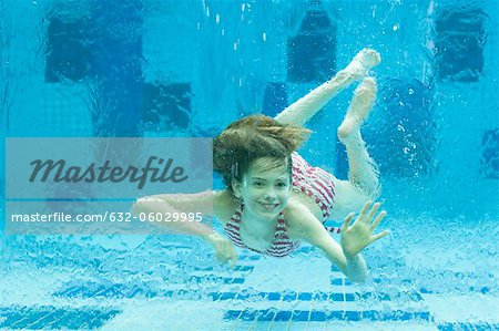 Girl swimming underwater in swimming pool Stock Photo - Premium Royalty-Free, Image code: 632-06029995