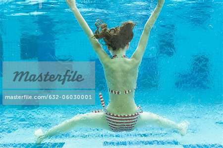 Girl swimming underwater in swimming pool, rear view Stock Photo - Premium Royalty-Free, Image code: 632-06030001