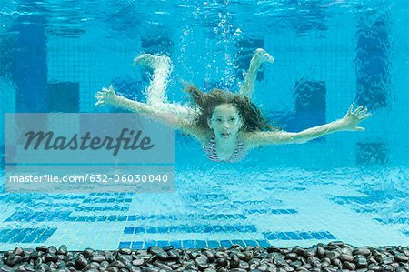 Girl swimming underwater in swimming pool Stock Photo - Premium Royalty-Free, Image code: 632-06030040