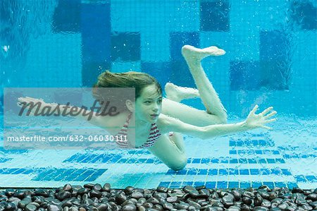 Girl swimming underwater in swimming pool Stock Photo - Premium Royalty-Free, Image code: 632-06030111