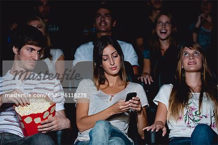 Woman using cell phone in movie theater, man looking over with annoyed expression Stock Photo - Premium Royalty-Free, Image code: 632-06118278