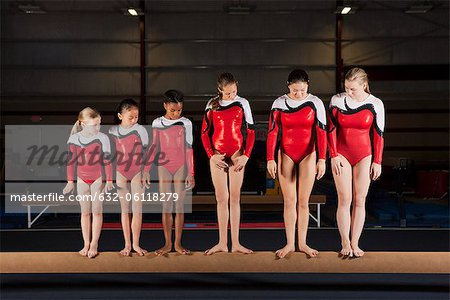 Female gymnasts of various ages standing in a row on balance beam Stock Photo - Premium Royalty-Free, Image code: 632-06118279