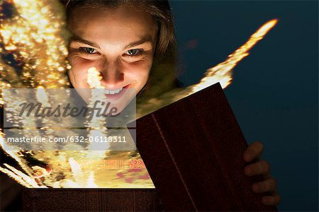 Young woman opening gift box containing glowing fireworks Stock Photo - Premium Royalty-Free, Image code: 632-06118311