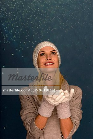 Woman wearing knit hat and gloves in front of snowy background, portrait Stock Photo - Premium Royalty-Free, Image code: 632-06118331
