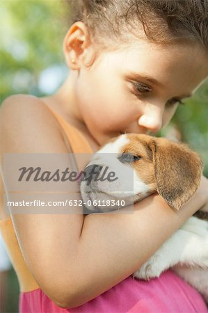 Girl kissing beagle puppy Stock Photo - Premium Royalty-Free, Image code: 632-06118340