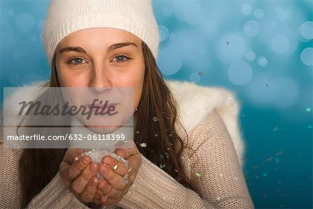 Young woman wearing winter clothing, holding handful of confetti, portrait Stock Photo - Premium Royalty-Free, Image code: 632-06118399