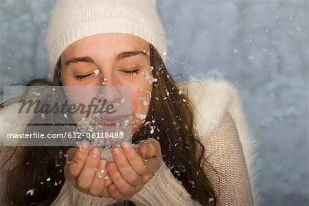 Young woman wearing winter clothing, blowing handful of confetti Stock Photo - Premium Royalty-Free, Image code: 632-06118488