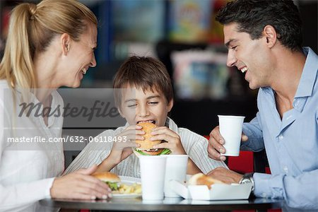 Boy eating hamburger in fast food restaurant with his parents Stock Photo - Premium Royalty-Free, Image code: 632-06118493