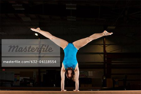Gymnast doing handstand with legs split Stock Photo - Premium Royalty-Free, Image code: 632-06118554