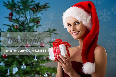 Woman wearing Santa hat and holding Christmas present, portrait Stock Photo - Premium Royalty-Free, Image code: 632-06118583
