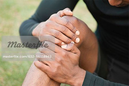 Man holding injured knee, cropped Stock Photo - Premium Royalty-Free, Image code: 632-06118662