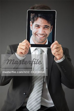 Man holding smiling photograph in front of his face Stock Photo - Premium Royalty-Free, Image code: 632-06118666