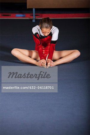 Gymnast sitting on floor stretching Stock Photo - Premium Royalty-Free, Image code: 632-06118701