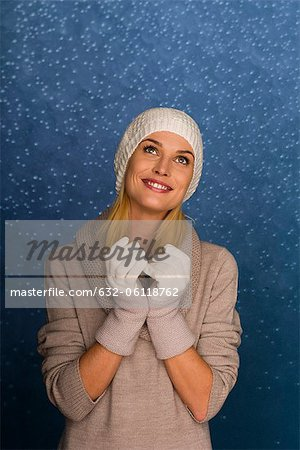 Woman wearing knit hat and gloves in front of snowy background, portrait Stock Photo - Premium Royalty-Free, Image code: 632-06118762