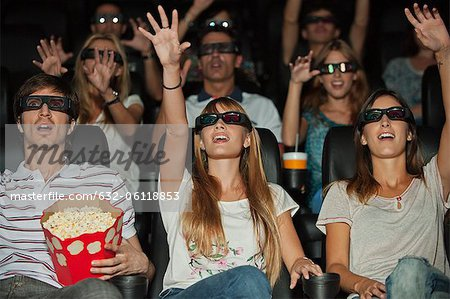 Audience wearing 3-D glasses in movie theater, arms reaching out Stock Photo - Premium Royalty-Free, Image code: 632-06118853