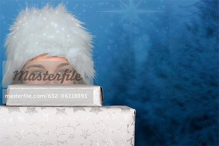 Young woman peeking over stack of Christmas gifts, portrait Stock Photo - Premium Royalty-Free, Image code: 632-06118891