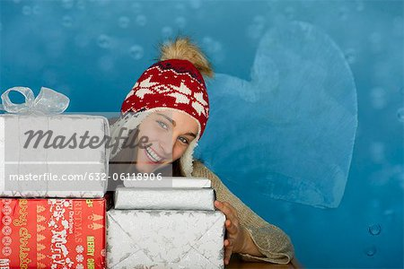 Young woman with stacks of Christmas gifts, portrait Stock Photo - Premium Royalty-Free, Image code: 632-06118906