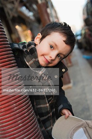 Boy peering around column at camera, portrait Stock Photo - Premium Royalty-Free, Image code: 632-06317260
