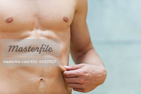 Barechested man pinching waist, mid section Stock Photo - Premium Royalty-Free, Image code: 632-06317527