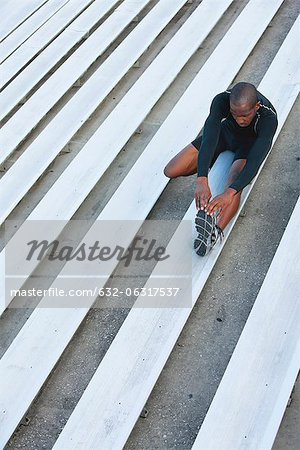 Man stretching on bleacher, high angle view Stock Photo - Premium Royalty-Free, Image code: 632-06317537