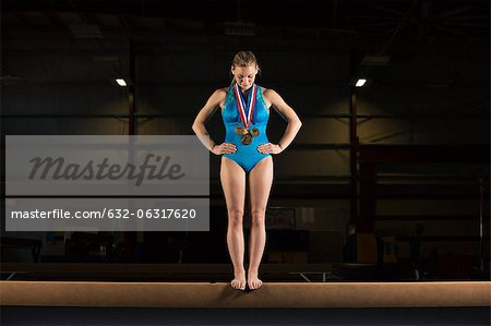 Gymnast with medals standing on balance beam Stock Photo - Premium Royalty-Free, Image code: 632-06317620