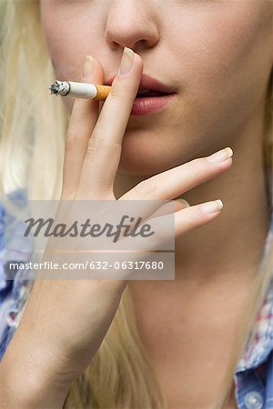 Young woman smoking cigarette, cropped Stock Photo - Premium Royalty-Free, Image code: 632-06317680