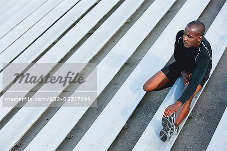Man stretching on bleacher, high angle view Stock Photo - Premium Royalty-Free, Image code: 632-06317699
