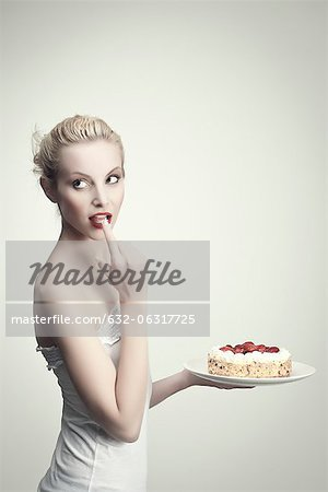 Young woman holding strawberry cake, licking cream off finger, portrait Stock Photo - Premium Royalty-Free, Image code: 632-06317725