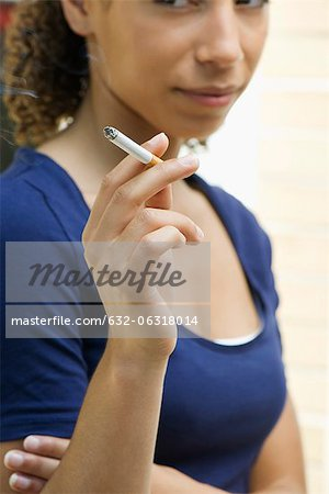 Young woman smoking cigarette Stock Photo - Premium Royalty-Free, Image code: 632-06318014