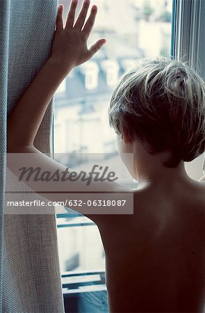 Boy looking out of window, rear view Stock Photo - Premium Royalty-Free, Image code: 632-06318087