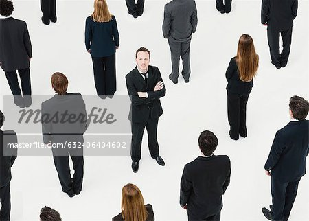 Businessman with arms crossed standing in midst of anonymously dressed business professionals Stock Photo - Premium Royalty-Free, Image code: 632-06404602
