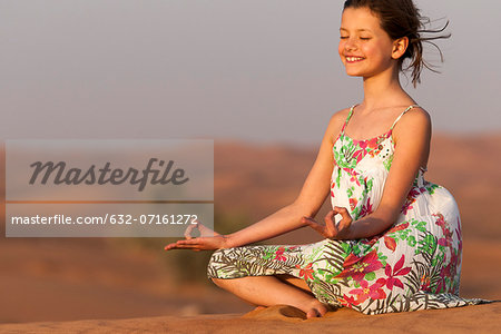 Girl meditating in desert Stock Photo - Premium Royalty-Free, Image code: 632-07161272