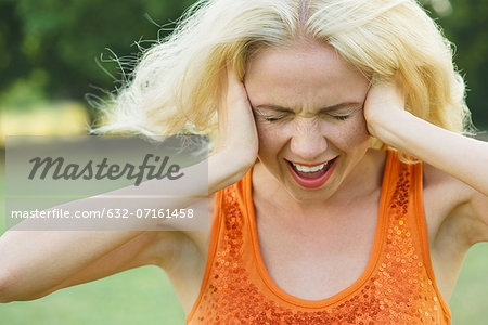Woman screaming with eyes closed and hands over ears Stock Photo - Premium Royalty-Free, Image code: 632-07161458