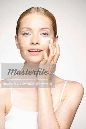 Young woman applying moisturizer under eye Stock Photo - Premium Royalty-Free, Image code: 632-07494940