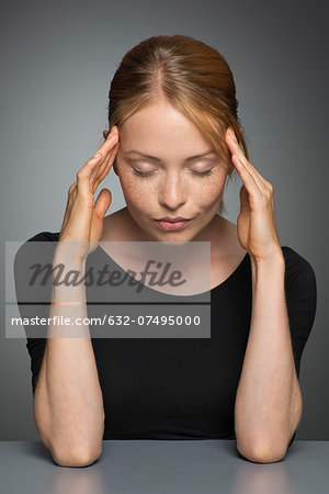 Young woman holding head, eyes closed Stock Photo - Premium Royalty-Free, Image code: 632-07495000