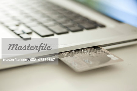 Credit card sticking out of side of laptop computer Stock Photo - Premium Royalty-Free, Image code: 632-07539887