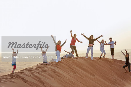 Group of people standing on top of desert dune with arms raised in air Stock Photo - Premium Royalty-Free, Image code: 632-07539890