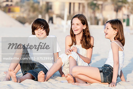 Siblings sitting together on sand at the beach Stock Photo - Premium Royalty-Free, Image code: 632-07539954