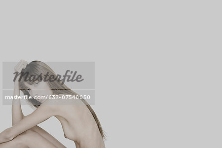 Nude young woman sitting with knees raised, hand on head, looking at camera Stock Photo - Premium Royalty-Free, Image code: 632-07540050