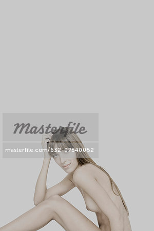Nude young woman sitting with knees raised, holding head, smiling at camera Stock Photo - Premium Royalty-Free, Image code: 632-07540052