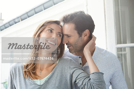 Couple whispering and smiling by window Stock Photo - Premium Royalty-Free, Image code: 632-07674436