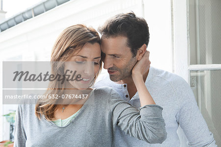 Couple embracing by open window Stock Photo - Premium Royalty-Free, Image code: 632-07674437
