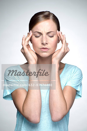 Young woman with headache holding head Stock Photo - Premium Royalty-Free, Image code: 632-07674440