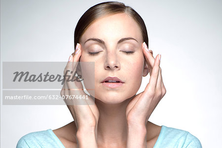 Young woman with headache holding head Stock Photo - Premium Royalty-Free, Image code: 632-07674441