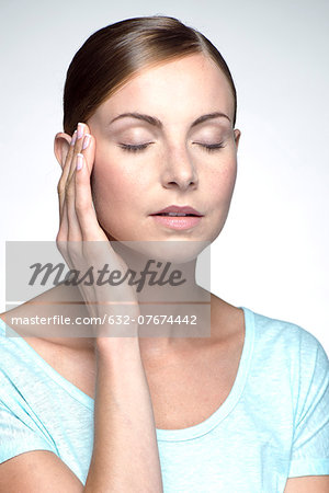Young woman with headache holding head Stock Photo - Premium Royalty-Free, Image code: 632-07674442